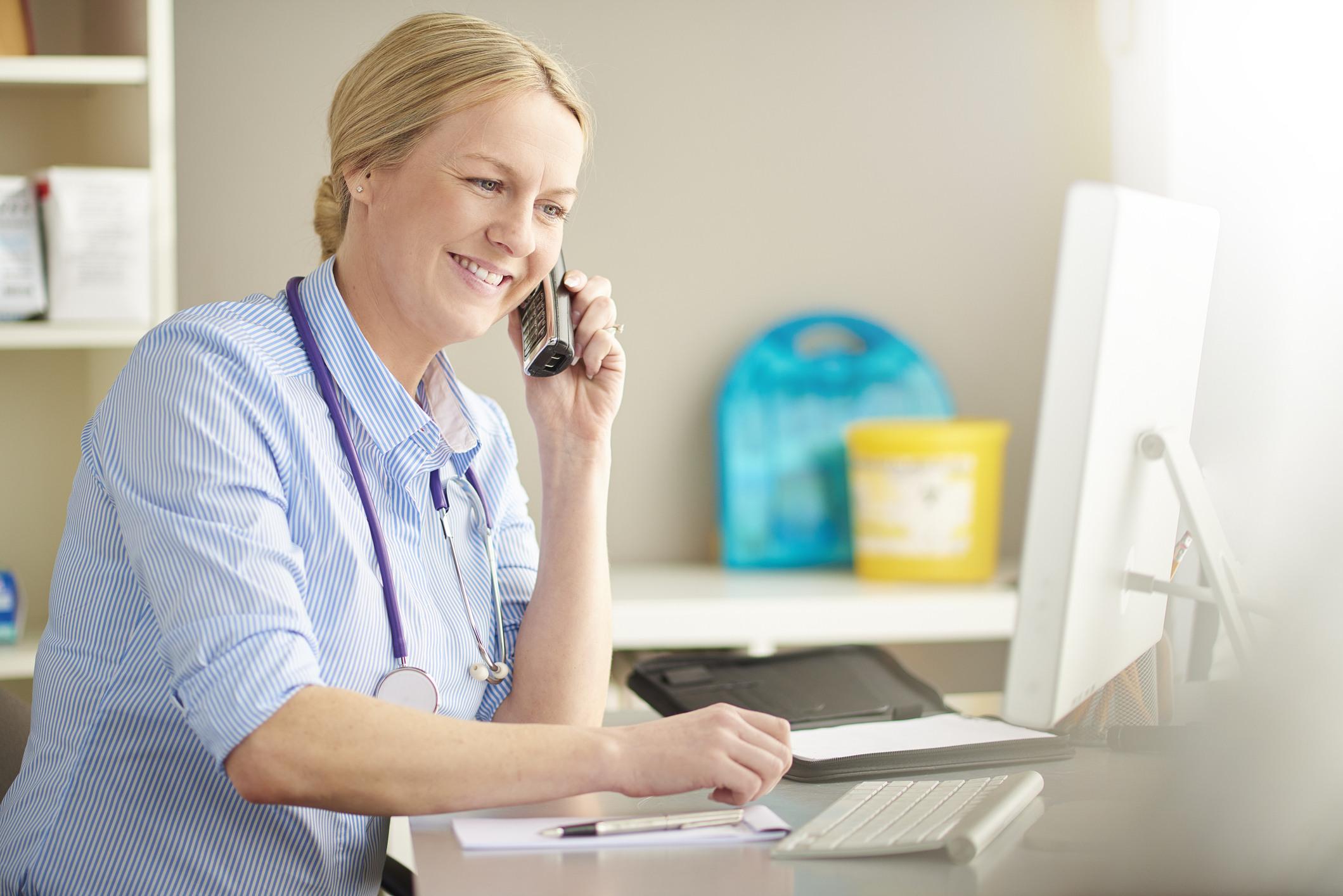 Female doctor at her desk, smiling while using the phone