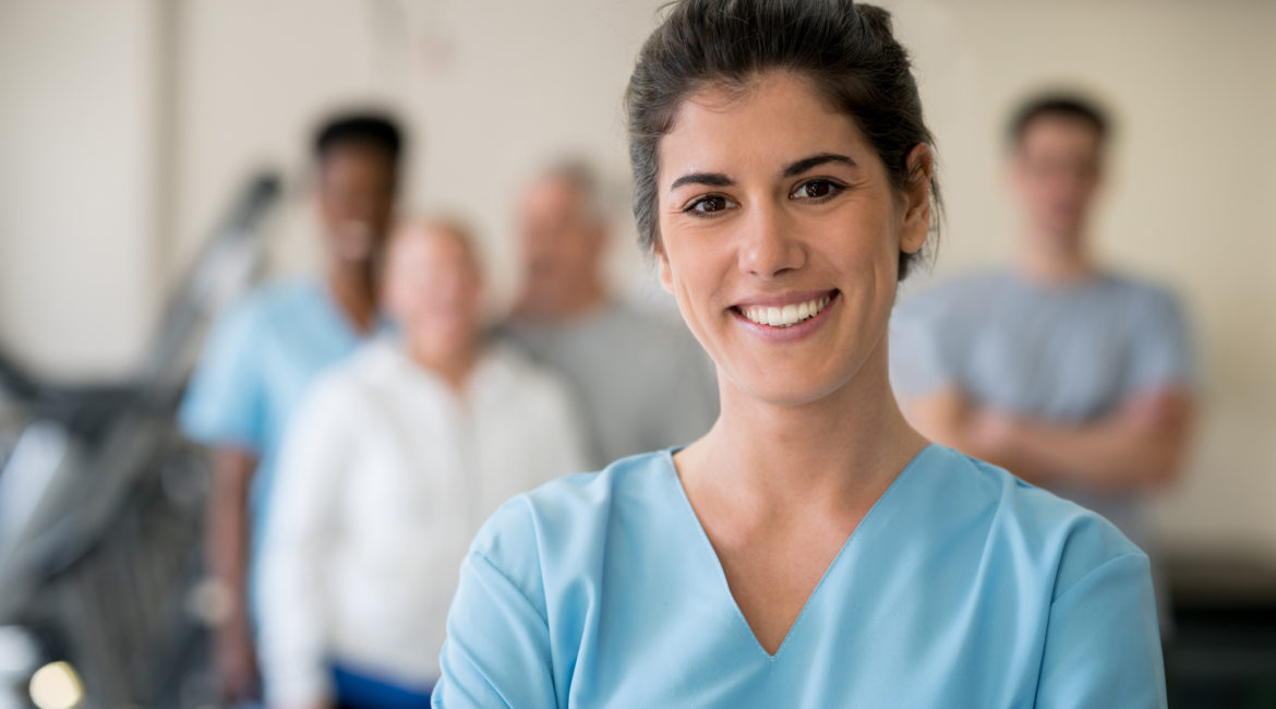 Female nurse smiling with medical team out of focus in the background